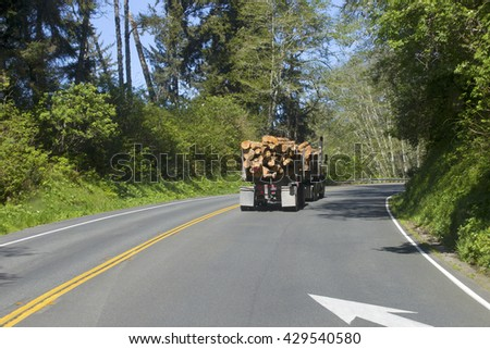 Logging truck on mountain highway, California