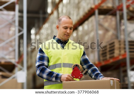 logistic, delivery, shipment, people and export concept - happy man in safety vest packing box or parcel with scotch tape at warehouse or mail storage - stock photo