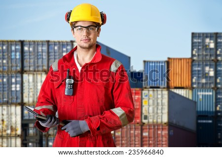 Logistics manager at a container transhipment plant, with an electronic tablet, and cb radio observing safety regulations - stock photo