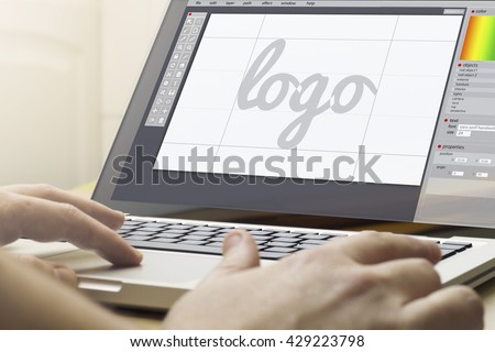 logo design concept: man using a laptop with logo design software on the screen. Screen graphics are made up. - stock photo