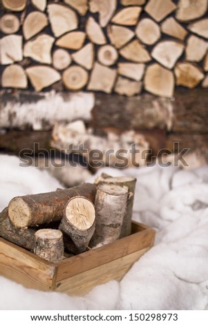 logs in a box in the snow on a background of a woodpile