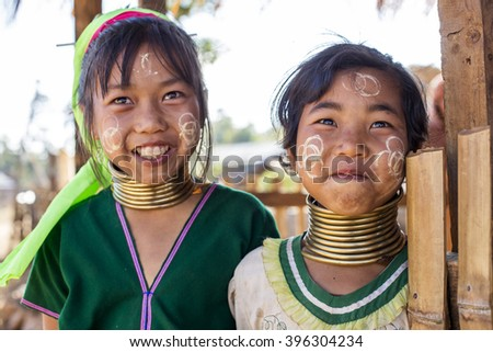 LOIKAW, MYANMAR - JANUARY 23, 2016: A portrait of a pair of smiling girls from the Padaung tribe (Karen) who are famous for wearing large brass coils around their neck.