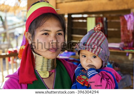 LOIKAW, MYANMAR - JANUARY 23, 2016: A portrait of a woman and baby from the Padaung tribe (Karen) who are famous for wearing large brass coils around their neck.