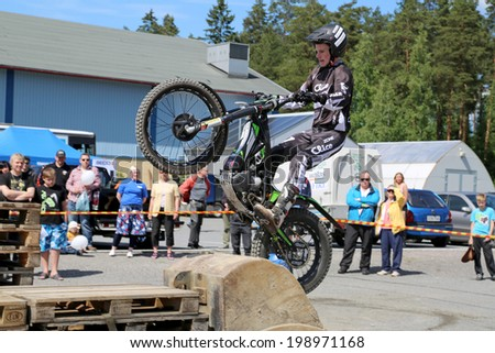 LOIMAA, FINLAND - JUNE 15, 2014: Finnish Champion Timo Myohanen gives the audience an exciting show in Motorcycle Trials at HeMa Show 2014 in Loimaa, Finland. - stock photo