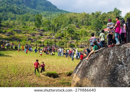 Lokomata, Indonesia - September 9, 2014: Group of people on rice field attending the ceremony of cleaning corpses in Lokomata, Tana Toraja, Sulawesi, Indonesia. - stock photo