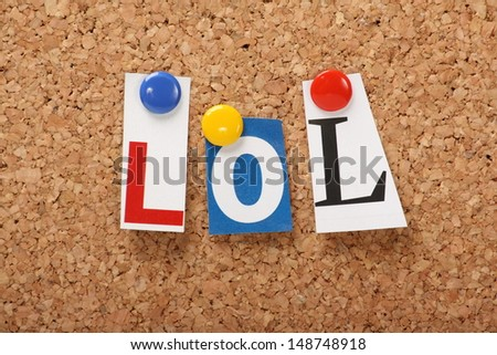 LOL the abbreviation for Laugh Out Loud in cut out magazine letters pinned to a cork notice board - stock photo
