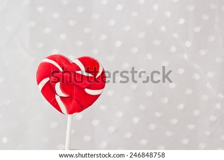 Lollipop in Heart Shape. Valentines Day Candy  on white fabric dot background - stock photo