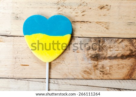 Lollipop with color of ukrainian flag, on wooden background. - stock photo