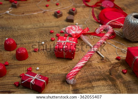 Lollipops, chocolate hearts and presents for Valentines day on wooden table