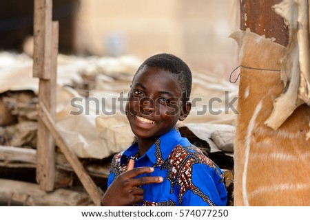 LOME, TOGO - Jan 9, 2017: Unidentified Togolese boy in blue shirt smiles at the Lome fetish market. Togo people suffer of poverty due to the bad economy