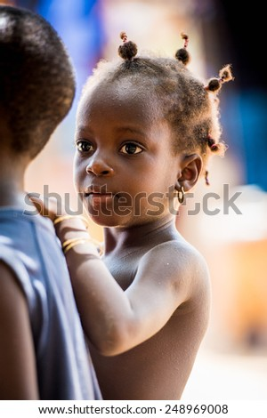 LOME, TOGO - MAR 9, 2013: Unidentified Togolese cute little girl with pigtails hugs her little friend. People of Togo suffer of poverty due to the unstable economic situation. - stock photo
