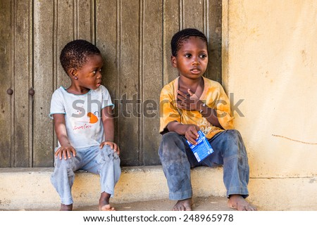 LOME, TOGO - MAR 9, 2013: Unidentified Togolese little boy and girl sit at the porch of a house. People of Togo suffer of poverty due to the unstable economic situation.