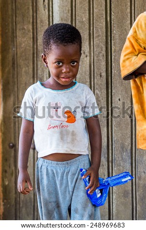 LOME, TOGO - MAR 9, 2013: Unidentified Togolese two little girsl sstay at the house. People of Togo suffer of poverty due to the unstable economic situation.