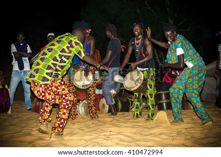 LOMPOUL/SENEGAL - NOVEMBER 12, 2013: Unidentified africans in colorful clothes play drums and dance during night in the camp at Lompoul desert, Senegal - stock photo