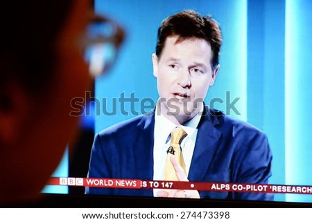 LONDON - APR 2: A viewer watches Liberal Democrat leader and Deputy Prime Minister Nick Clegg on a live general election TV debate on Apr 2, 2015 in London, UK. Voters go to the polls on May 7. - stock photo