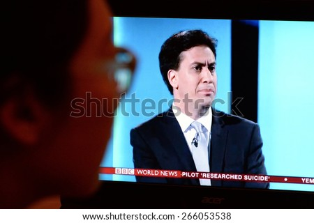 LONDON - APR 4:  A viewer watches opposition party Labour leader Ed Miliband on an election TV debate on Apr 4, 2015 in London, UK. Political parties joined the live TV debate ahead of polls on May 7. - stock photo