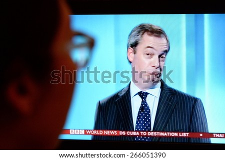 LONDON - APR 4:  A viewer watches UKIP leader Nigel Farage on an election TV debate on Apr 4, 2015 in London, UK. Major political parties joined the live TV debate ahead of polls on May 7. - stock photo