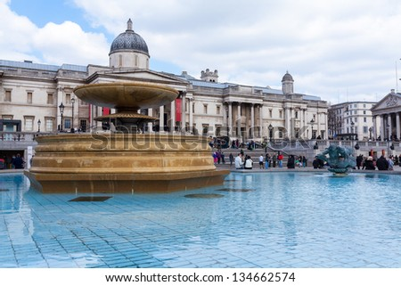 LONDON - APR 3 : Trafalgar square and fountain pictured on April 3rd, 2013, in London, UK. It is one of the most popular tourist attraction worldwide with more than 15 million visitors per year. - stock photo