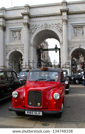 LONDON - APRIL 7 : A London Taxi at Marble Arch on April 7, 2013 in London, UK. Not all London cabs are black, but all  undergo a strict annual mechanical test before they are allowed to ply for hire. - stock photo
