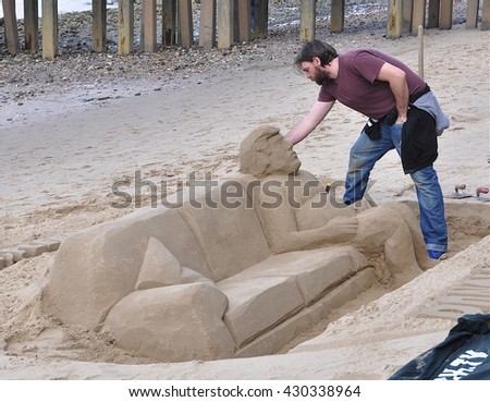 LONDON - APRIL 30, 2016. A sculptor creates Donald Trump in sand while the tide is out on the south bank of the River Thames in central London, UK.  - stock photo