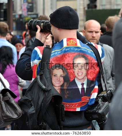 LONDON - APRIL 29: An unidentified photographer wears a 'Kate and Wills waistcoat and captures the crowd celebrating the wedding of Prince William and Catherine Middleton in Trafalgar Square on April 29, 2011 in London, England. - stock photo