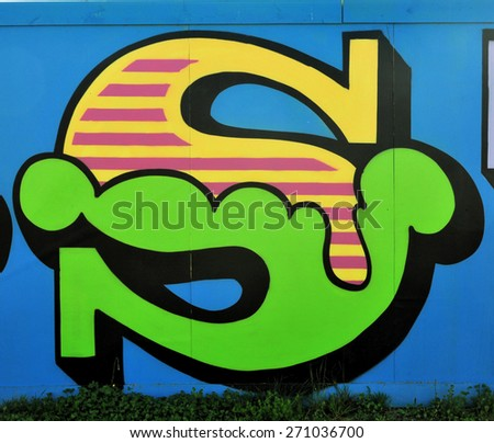 LONDON - APRIL 18, 2015. Circus style typographic street art by British artist Ben Eine decorates temporary timber hoarding in the park at Stratford, east London, UK. - stock photo