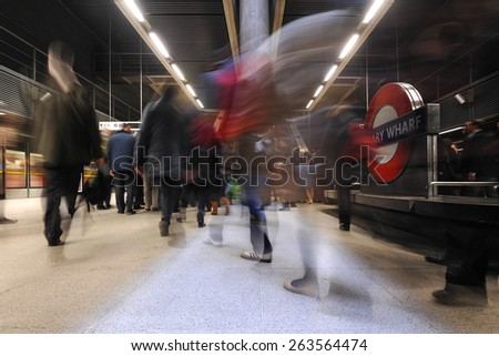 LONDON - APRIL 10. 2013: Commuters inside Canary Wharf Station. It is the busiest station on the London Underground with over 40 million passengers each year. - stock photo