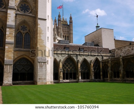 LONDON - APRIL 21: Courtyard of Westminster Abbey with Houses of Parliament in the background on April 21, 2012 in London. The abbey is the venue for many royal occasions like weddings and coronations - stock photo