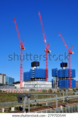 LONDON - APRIL 18, 2015. Cranes dominate the landscape at Stratford; part of a huge residential, leisure and commercial regeneration programme from industrial wasteland in east London, UK. - stock photo