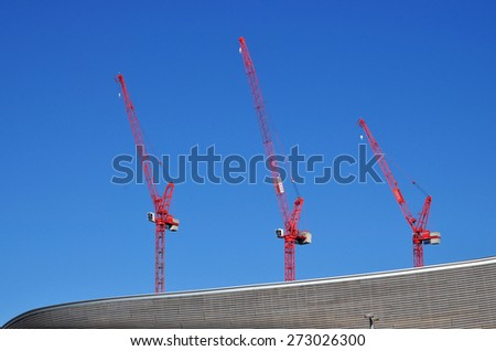 LONDON - APRIL 18, 2015. Cranes transform the landscape of Stratford; part of a huge regeneration programme from industrial wasteland in the Borough of Newham, London, UK. - stock photo