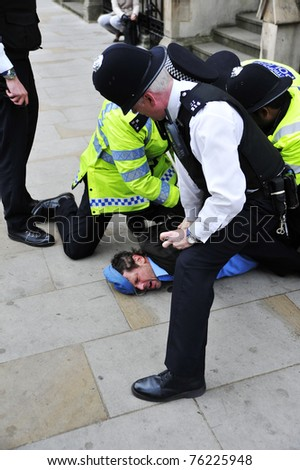 LONDON - APRIL 29 - Police detain an unidentified man for breaking through the security cordon at the Royal Wedding of Prince William and Kate Middleton at Westminster Abbey in London, England. - stock photo
