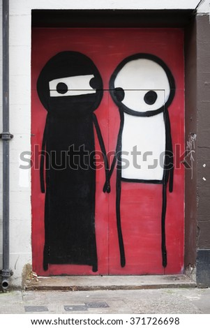 LONDON - APRIL 11, 2015. Street art by Stik in a doorway at Shoreditch in the Borough of Tower Hamlets, an area renown for its public painting and poster art in east London, UK. - stock photo