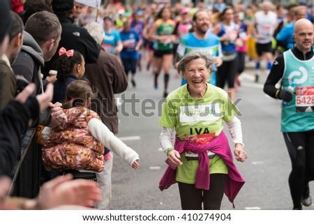 LONDON - April 24 2016. The London Marathon. Elderly lady enjoying the atmosphere whilst running the marathon. - stock photo