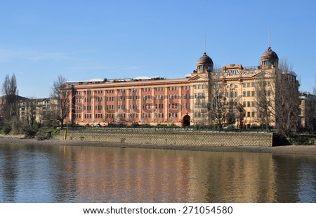 LONDON - APRIL 7, 2015. The old Harrods Furniture Depository overlooking the River Thames was built for storing large retail products, but now converted to apartments located at Barnes, west London. - stock photo
