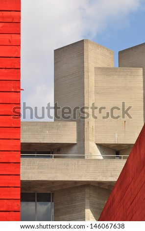 LONDON - APRIL 6. The permanent grey brutalist concrete National Theatre building contrasts with the red timber clad temporary theatre known as 'The Shed', April 6, 2013, at the Southbank, London, UK. - stock photo