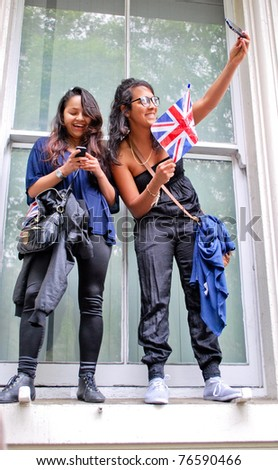 LONDON - APRIL 29: Two girls with a flag standing near the window of a building next to the Buckingham Palace on April 29. April 29, 2011 in London, England. - stock photo