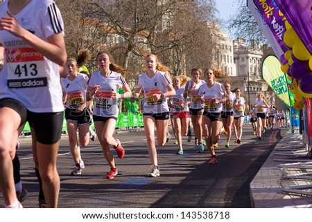 LONDON - APRIL 13: Unidentified girls run the London marathon on April 13th, 2013 in London, England, UK. The marathon is an annual event. - stock photo