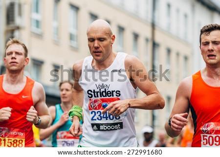 LONDON - APRIL 26: Unidentified man runs the Virgin Money London Marathon on April 26, 2015 in Isle of Dogs, London, England, UK. - stock photo