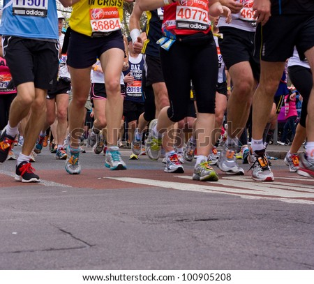 LONDON - APRIL 22: Unidentified people run the London marathon on April 22, 2012 in London, England, UK. The marathon is an annual event. - stock photo