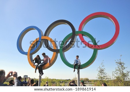 LONDON - APRIL 16. Visitors enjoying the Olympic Games symbol in the new Queen Elizabeth Olympic Park, on April 16, 2014, a legacy from the games in the parkland now open at Stratford, London. - stock photo