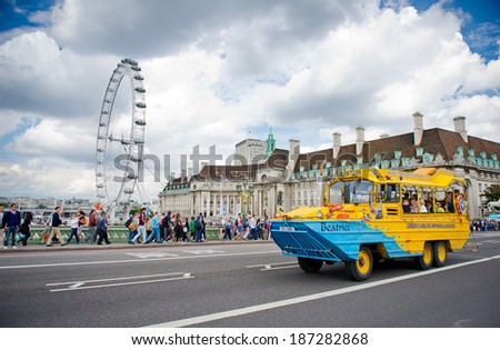 LONDON-AUG 6: Duck tour bus with London Eye in background on Aug. 6, 2012 in London, England. Duck tour buses are amphibious vehicles. Duck tours are primarily offered as tourist attractions in London - stock photo
