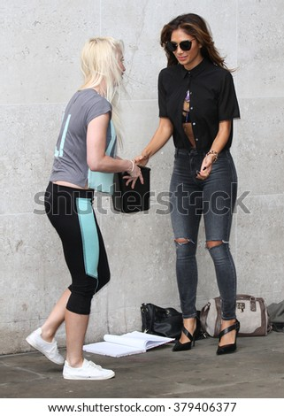 LONDON - AUG 26, 2014: Nicole Scherzinge pours water over fan Steffie Croxon for the ALS Ice Bucket Challenge as she leaves the BBC Radio one studios on Aug 26, 2014 in London