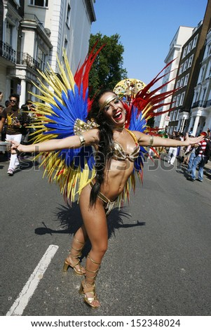 LONDON - AUG 26: Participant with carnival costume in the second day of Notting Hill Carnival, largest in Europe, on August 26, 2013 in London, UK. Carnival takes place over two days in every August - stock photo