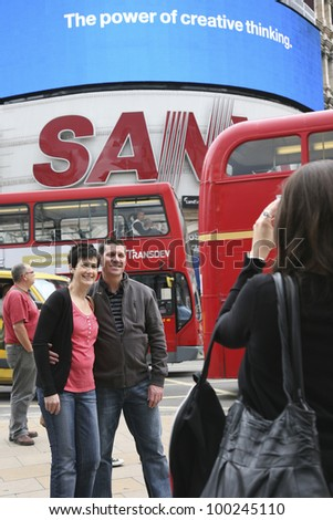 LONDON - AUG 12: Tourists in Piccadilly Circus, famous tourist attraction, road junction, built in 1819, links to West End, Regent Street, Haymarket, Leicester Square, on Aug 12, 2010 in London, UK. - stock photo