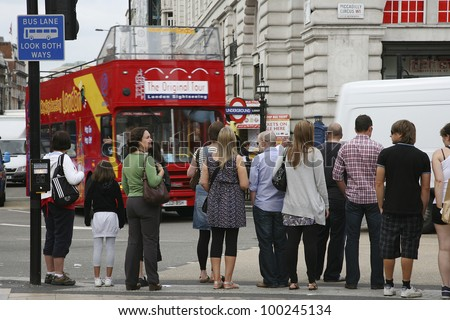 LONDON - AUG 9: Tourists in Piccadilly Circus, famous tourist attraction, road junction, built in 1819, links to West End, Regent Street, Haymarket, Leicester Square, on Aug 9, 2010 in London, UK. - stock photo