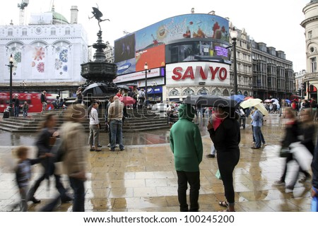LONDON - AUG 13: Tourists in Piccadilly Circus, famous tourist attraction, road junction, built in 1819, links to West End, Regent Street, Haymarket, Leicester Square, on Aug 13, 2010 in London, UK. - stock photo