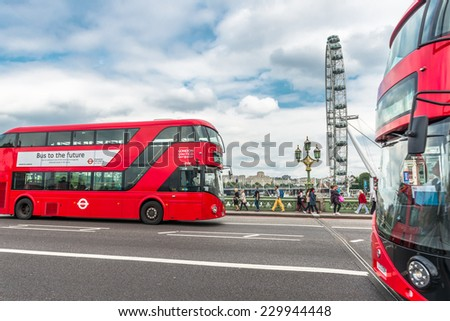 LONDON - AUGUST 27, 2014: Buses and tourists cross the Westminster Bridge in front of the London Eye, Europe's tallest Ferris wheel on the South Bank of the River Thames, a famous tourist attraction - stock photo