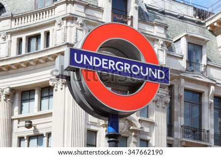 LONDON - AUGUST 6, 2015: Famous London underground sign with white architecture background. The tube logo was registered as a trademark in 1917 on August 6, 2015 in London.