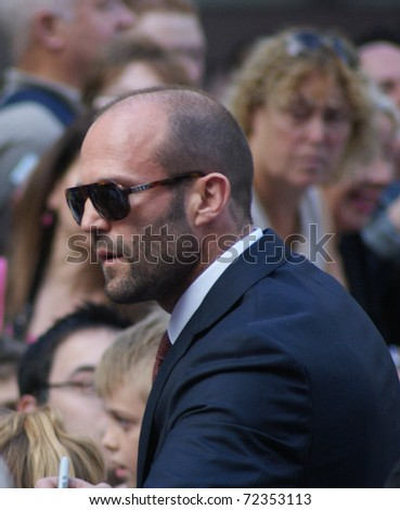 LONDON - AUGUST 9: Jason Statham greets fans as he arrives at the UK Premiere of 'The Expendables' in Leicester Square on August 9, 2010 in London - stock photo