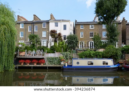 LONDON - AUGUST 8: Little Venice canal, houses and house boat in a summer day on August 8, 2015 in London, UK. This is a typical part of London, known for its canals and moored boats. - stock photo